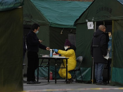 Residents line up for coronavirus tests at tents set up on the streets of Beijing on Sunday, Dec. 27, 2020. Beijing has urged residents not to leave the city during the Lunar New Year holiday in February, implementing new restrictions and mass testings after several coronavirus infections last week. (AP …