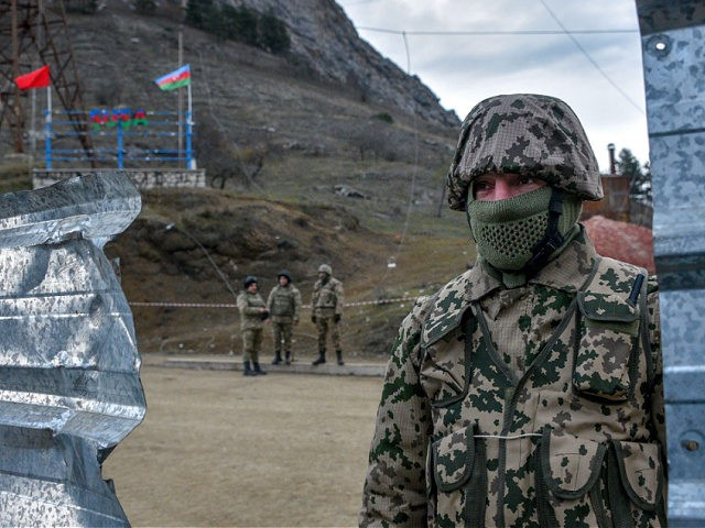 Azerbaijani soldiers patrol at a checkpoint on a road outside the town of Shusha on November 26, 2020, after six weeks of fighting between Armenia and Azerbaijan over the disputed Nagorno-Karabakh region. - A Moscow-brokered peace deal was announced on November 10 after Azerbaijan's military overwhelmed Armenian separatist forces and …