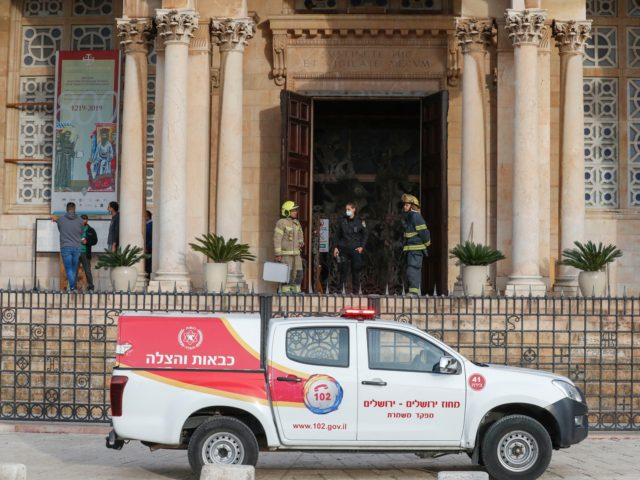 """Israeli police and firefighters stand at the entrance of the Church of All Nations in the Garden of Gethsemane in east Jerusalem after an arson attempt, on December 4, 2020. - Israeli police said in a statement they were questioning a 49-year-old suspect who had """"poured flammable liquid inside the …"""
