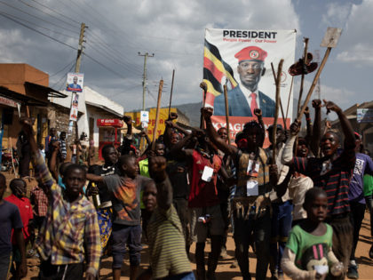 MBALE, UGANDA - DECEMBER 29: People parade with a Bobi Wine poster during a circumcision ceremony on December 29, 2020 in Mbale, Uganda. Bobi Wine is taking on incumbent president Yoweri Museveni on the January 14 2021 election. Imbalu is a biannual community tradition of the Bagisu tribe in eastern …