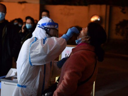 This photo taken on December 8, 2020 shows a health worker conducting a nucleic acid test on a resident in Chengdu, in western China's Sichuan province, after new Covid-19 coronavirus cases were detected in the city. (Photo by STR / AFP) / China OUT (Photo by STR/AFP via Getty Images)