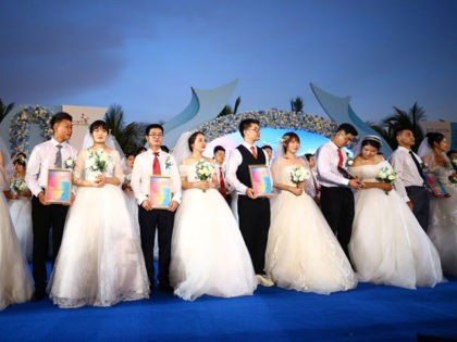This photo taken on June 6, 2020 shows couples during a mass wedding ceremony for couples who had delayed their weddings to work on the frontlines of the fight against the COVID-19 coronavirus, in Sanya, on China's southern Hainan island. - One hundred couples from across China took opart in …