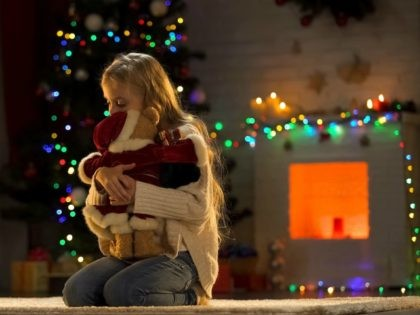 Upset girl embracing teddy bear, abandoned child in orphanage at Christmas - stock photo