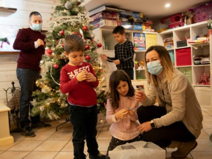 Maurizio Di Giacobbe, left, and Glenda Grossi, right, place decorations on a Christmas tree, with their children from left, Tiziano, 4, Arianna, 9, and Flavio 10, in their house in the outskirts of Rome, Saturday Dec. 12, 2020. The coronavirus pandemic has posed unprecedented challenges for families around the world …