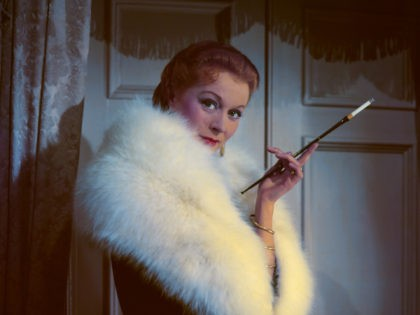 A model wearing a fur coat and smoking using a cigarette holder, circa 1950. (Photo by Hulton Archive/Getty Images)