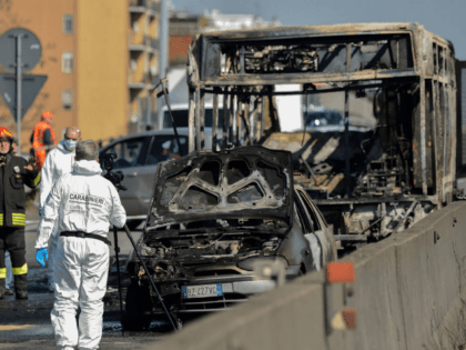 TOPSHOT - Forensic policemen and firefighters work by the wreckage of a school bus that was transporting some 50 children on March 20, 2019 after it was torched by the bus' driver, in San Donato Milanese, southeast of Milan. - Italian police rescued some 50 children on March 20, 2019 …