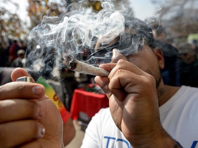 """A demonstrator smokes marijuana during the """"Cultivate Your Rights"""" march demanding its legalization, in Santiago, on May 18, 2019. (Photo by Martin BERNETTI / AFP) (Photo credit should read MARTIN BERNETTI/AFP via Getty Images)"""
