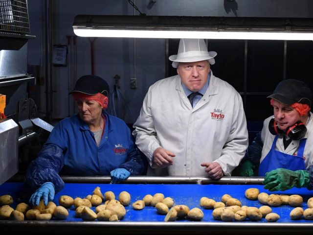 ARMAGH, NORTHERN IRELAND - NOVEMBER 07: Prime Minister Boris Johnson (C) helps quality control staff during a general election campaign visit to the Tayto Castle crisp factory on November 07, 2019 in County Armagh, Northern Ireland, United Kingdom. (Photo by Daniel Leal-Olivas - WPA Pool/Getty Images)