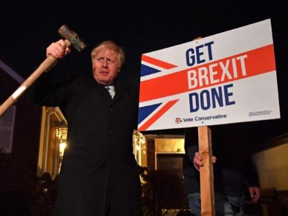 "TOPSHOT - Britain's Prime Minister and Conservative party leader Boris Johnson poses after hammering a ""Get Brexit Done"" sign into the garden of a supporter, with a sledgehammer as he campaigns with his team in Benfleet, east of London on December 11, 2019, the final day of campaigning for the …"