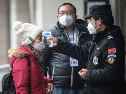 "WUHAN, CHINA - JANUARY 22: (CHINA OUT) Security personnel check the temperature of passengers in the Wharf at the Yangtze River on January 22, 2020 in Wuhan, Hubei province, China. A new infectious coronavirus known as ""2019-nCoV"" was discovered in Wuhan as the number of cases rose to over 400 …"
