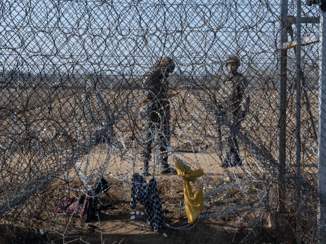 EDIRNE, TURKEY - MARCH 01: Greek border guards stands behind the border fences on March 01, 2020 in Edirne, Turkey. Refugees and migrants from various countries board a boat in an attempt to reach Greece from Turkey by crossing the Evros River on March 01, 2020 in Edirne, Turkey. Thousands …