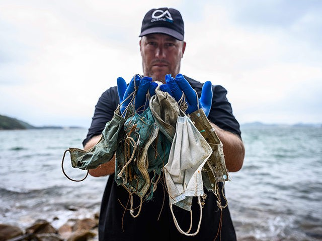 In this photo taken on May 13, 2020, Gary Stokes, founder of the environmental group Oceans Asia, poses with discarded face masks he found on a beach in the residential area of Discovery Bay on the outlying Lantau island in Hong Kong. - Surgical masks are washing up in growing …