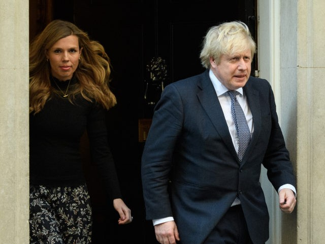 LONDON, UNITED KINGDOM - MAY 14: Britain's Prime Minister Boris Johnson and his partner Carrie Symonds stand outside the door of number 10 Downing Street as they thank the key workers who are working during the current lockdown on May 14, 2020 in London, United Kingdom. Following the success of …