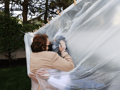 Michelle Grant (R) hugs her mother, Mary Grace Sileo through a plastic drop cloth hung up on a homemade clothes line during Memorial Day Weekend on May 24, 2020 in Wantagh, New York. It is the first time they have had physical contact of any kind since the coronavirus COVID-19 …