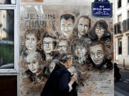 TOPSHOT - A woman walks past a painting by French street artist and painter Christian Guemy, known as C215, in tribute to members of Charlie Hebdo newspaper who were killed by jihadist gunmen in January 2015, in Paris, on August 31, 2020. - Fourteen alleged accomplices in the 2015 jihadist …