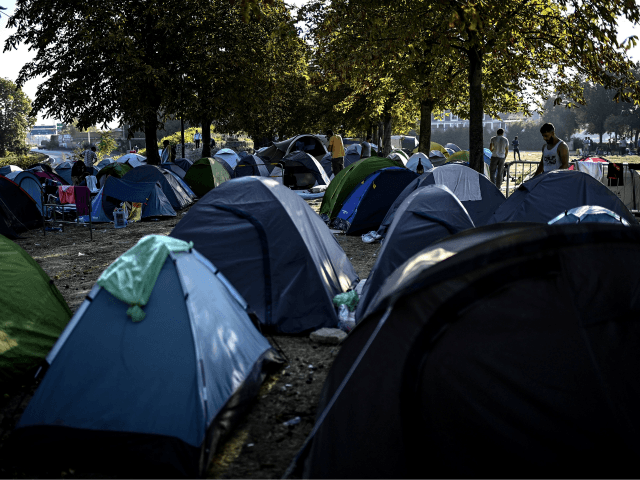 Asylum seekers, mainly from Afghanistan, stand by their tents at a makeshift migrant camp set below the A1 highway in the north of Paris' popular suburb of Saint-Denis on September 16, 2020. (Photo by Christophe ARCHAMBAULT / AFP) (Photo by CHRISTOPHE ARCHAMBAULT/AFP via Getty Images)