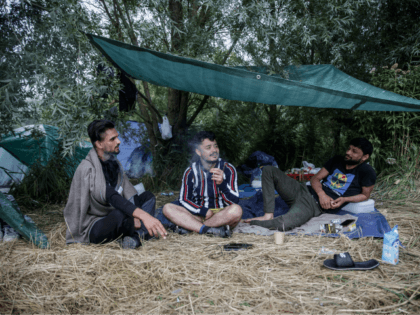 Migrants from Afghanistan sit under a semi-tent as they talk and smoke at a makeshift camp in the outskirts of Calais, northern France, on August 14, 2020. - The number of migrants crossing the English Channel -- which is 33,8 km (21 miles) at the closest point in the Straits …