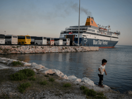 A child plays by the sea as hundreds of refugees from the islands of Lesbos, Chios, Samos, Kos and Leros wait to board buses after disembarking at the port of Lavrio, some 70 km south-east of Athens, prior to be transferred to camps in mainland Greece, on September 29, 2020. …