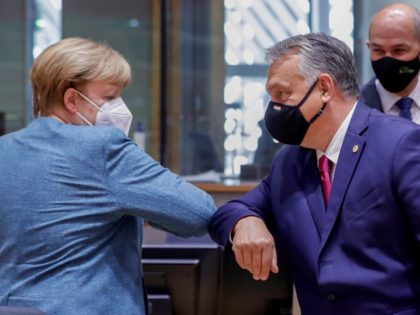 German Federal Chancellor Angela Merkel and Hungarian Prime Minister Viktor Orban (R) bump elbows as they arrive for an EU summit at the European Council building in Brussels, on October 1, 2020. - European Union leaders are meeting to address a series of foreign affairs issues ranging from Belarus to …