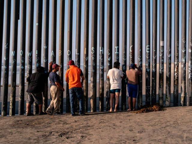 Men look through the US-Mexico border fence in Playas de Tijuana, Baja California state, Mexico, on October 3, 2020, amid the COVID-19 coronavirus pandemic. - This weekend the beach in Playas de Tijuana reopened with restrictions to visitors, after it was closed as a preventive measure to avoid the spread …