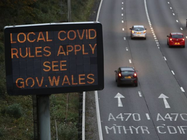 Traffic passes a COVID-19 sign displayed along the M4 motorway in southeast Wales on October 17, 2020, as further restrictions come into force as the number of novel coronavirus COVID-19 cases rises. - Wales's First Minister Mark Drakeford, announced Wednesday that Welsh police forces will carry out extra patrols on …