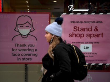 A pedestrian walks past posters advising customers to wear a face mask or covering due to the COVID-19 pandemic, as she walk past a temporarily closed-down shop on an almost deserted Oxford Street in London on November 26, 2020. - Britain's government on Wednesday unveiled plans to slash the foreign …