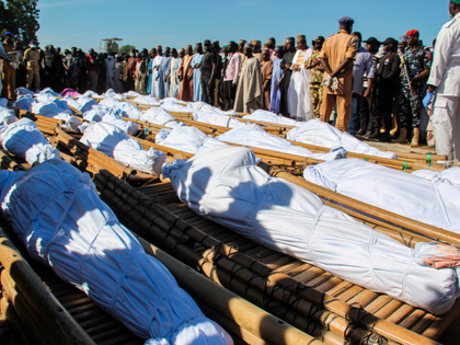 Mourners attend the funeral of 43 farm workers in Zabarmari, about 20km from Maiduguri, Nigeria, on November 29, 2020 after they were killed by Boko Haram fighters in rice fields near the village of Koshobe on November 28, 2020. - The assailants tied up the agricultural workers and slit their …