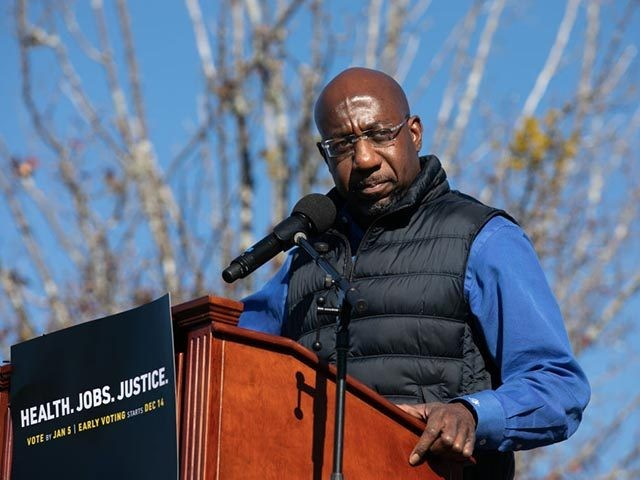 CONYERS, GA - DECEMBER 05: Democratic U.S. Senate candidate Raphael Warnock speaks to the crowd during an outdoor drive-in rally on December 5, 2020 in Conyers, Georgia. Warnock will face Republican candidate Sen. Kelly Loeffler (R-GA) in a runoff election that will take place January 5th. (Photo by Jessica McGowan/Getty …
