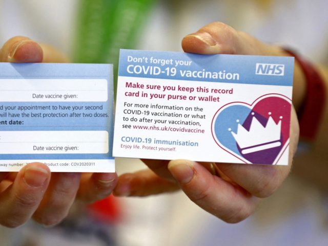 A model holds a card which will be given to patients following their vaccination for COVID-19 at Croydon University Hospital in south London on December 5, 2020, where the first batch of COVID-19 vaccinations has been delivered to the area. - Britain has pre-ordered 40 million doses of the Pfizer-BioNTech …