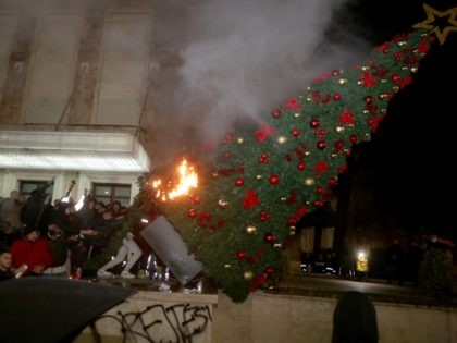 TOPSHOT - Protesters burn a Christmas tree in front of the Albanian Prime Minister building during clashes in Tirana on December 9, 2020. - Albanian police fired tear gas in Tirana late on December 9, 2020, at hundreds of protesters angry at the police for allegedly killing a young man …