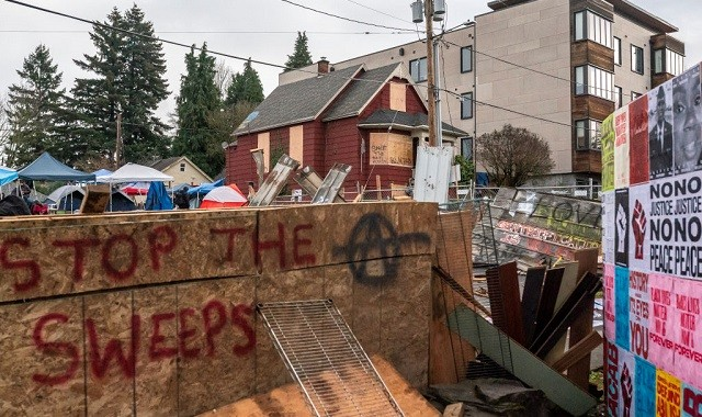 PORTLAND, OR - DECEMBER 09: Layers of chainlink fence and wood block the entry to the Red House on Mississippi Street on December 9, 2020 in Portland, Oregon. Police and protesters clashed during an attempted eviction Tuesday morning, leading protesters to establish a barricade around the Red House. (Photo by Nathan Howard/Getty Images)