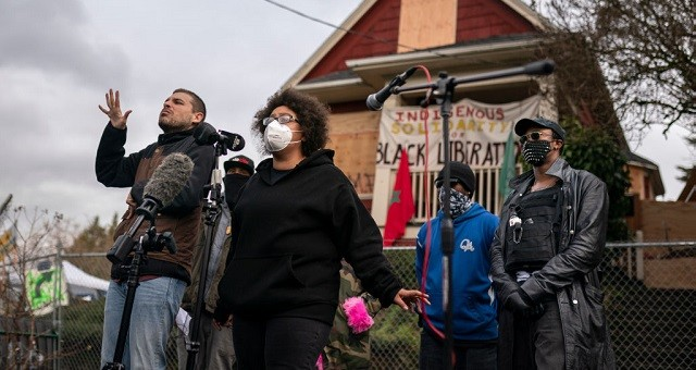 PORTLAND, OR - DECEMBER 09: Activists and the Kinney family speak to the press about the citys attempted eviction of residents from the Red House on Mississippi Ave on December 9, 2020 in Portland, Oregon. Police and protesters clashed during an attempted eviction Tuesday, leading protesters to establish a barricade around the Red House. (Photo by Nathan Howard/Getty Images)