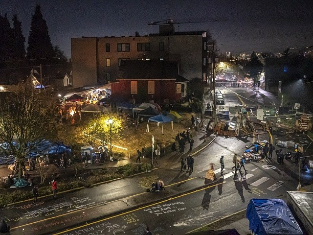 PORTLAND, OR - DECEMBER 09: Protesters walk through an area near the Red House on Mississippi Street blockaded against a police response on December 9, 2020 in Portland, Oregon. Police and protesters clashed during an attempted eviction Tuesday morning, leading protesters to establish a barricade around the Red House. (Photo by Nathan Howard/Getty Images)