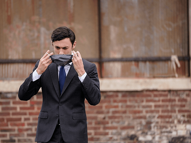 U.S. Democratic Senate candidate Jon Ossoff puts his face mask back on after delivering remarks during a campaign rally with U.S. President-elect Joe Biden at Pullman Yard on December 15, 2020 in Atlanta, Georgia. Biden's stop in Georgia comes less than a month before the January 5 runoff election for …