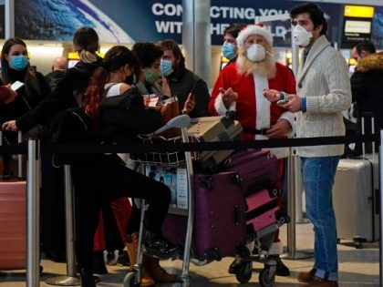 Travellers, one dressed in a Father Christmas outfit and all wearing face coverings, queue with their luggage in the departures hall at Terminal 2 of Heathrow Airport in west London on December 21, 2020, as a string of countries around the world banned travellers arriving from the UK, due to …