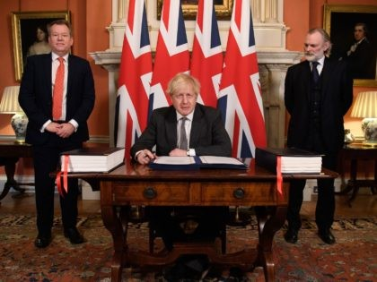 Britain's Prime Minister Boris Johnson (C) flanked by UK chief trade negotiator David Frost (L) and British Ambassador to the EU Tim Barrow (R) signs the Trade and Cooperation Agreement between the UK and the EU, the Brexit trade deal, at 10 Downing Street in central London on December 30, …