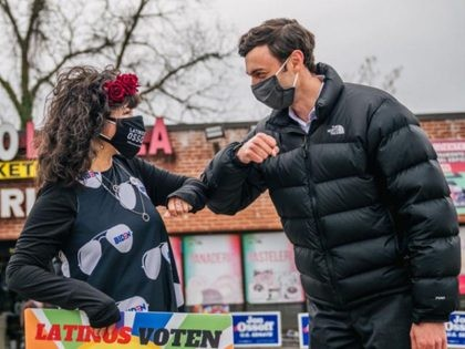 MARIETTA, GA - DECEMBER 30: Democratic Senate candidate Jon Ossoff elbow greets a woman at a Latino meet and greet and literature distribution rally on December 30, 2020 in Marietta, Georgia. In the lead-up to the January 5 runoff election, Democratic Senate candidate Jon Ossoff continues to focus on early …
