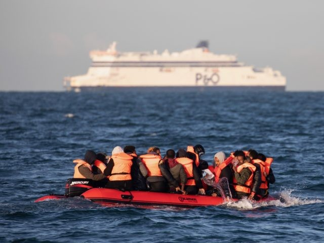 AT SEA, UNITED KINGDOM - SEPTEMBER 07: Migrants packed tightly onto a small inflatable boat bail water out as they attempt to cross the English Channel near the Dover Strait, the world's busiest shipping lane, on September 07, 2020 off the coast of Dover, England. Last Wednesday, more than 400 …