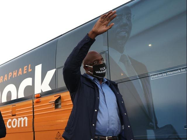 "COLUMBUS, GEORGIA - OCTOBER 29: Democratic U.S. Senate candidate Rev. Raphael Warnock stands next to his campaign bus as he prepares to speak during a ""Get Out the Early Vote"" drive-in campaign event on October 29, 2020 in Columbus, Georgia. With less than a week to go until Election Day, …"