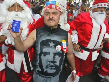 "A supporter of President Hugo Chavez holds a copy of the constitution by a man dressed as Santa Claus, during an activity organized for ""chavista"" children, in Caracas, 24 December 2002. Un partidario del presidente venezolano Hugo Chávez, con la figura del Che Guevara impresa en la camiseta y sosteniendo …"