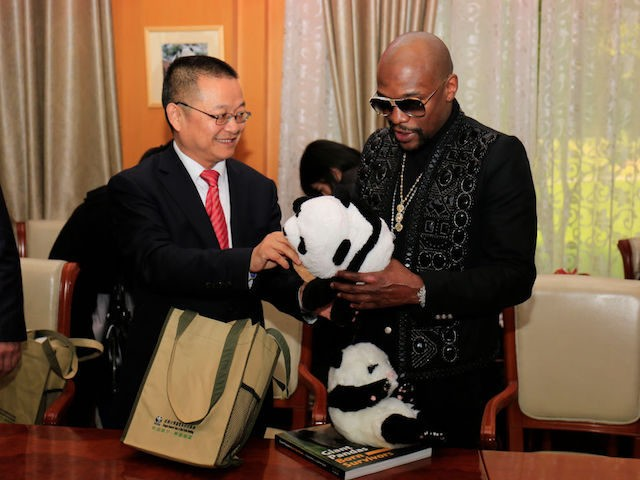 This picture taken on November 30, 2017 shows US boxer Floyd Mayweather (R) receiving a stuffed panda toy during an adoption ceremony after he adopted a panda baby at the Chengdu Research Base of Giant Panda Breeding in Chengdu in China's southwestern Sichuan province. Floyd Mayweather displayed his softer side …