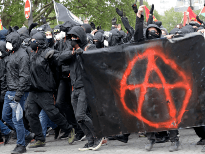 Protestors dressed in black and with the face covered, hold a banner picturing the symbol of the Anarchist as they take part in a march for the annual May Day workers' rally, in Paris, on May 1, 2018. (Photo by Thomas SAMSON / AFP) (Photo credit should read THOMAS SAMSON/AFP …