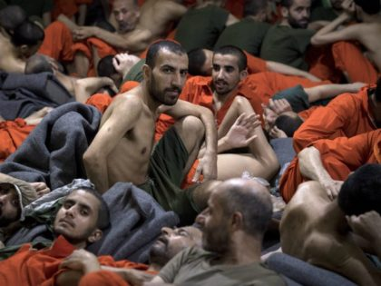 Men, accused of being affiliated with the Islamic State (IS) group, sit on the floor in a prison in the northeastern Syrian city of Hasakeh on October 26, 2019. - Kurdish sources say around 12,000 IS fighters including Syrians, Iraqis as well as foreigners from 54 countries are being held …