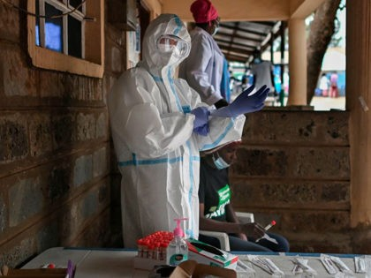 A health worker dressed in personal protective equipment (PPE) prepares to test someone during a mass testing for COVID-19 coronavirus provided free of charge by the Kenyan government in the Kibera slum in Nairobi on October 18, 2020. - The Nairobi Metropolitan Services (NMS) commenced a free COVID-19 coronavirus mass …