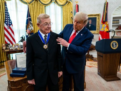 WASHINGTON, DC - DECEMBER 03: President Donald Trump presents the Medal of Freedom to former college football coach Lou Holtz in the Oval Office of the White House on December 3, 2020 in Washington, DC. Holtz is best known for his time as head coach of University of Notre Dame's …