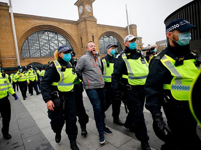 Police officers wearing protective face coverings to combat the spread of the coronavirus covid-19 take away a protester ahead of an anti-lockdown protest against government restrictions designed to control or mitigate the spread of the novel coronavirus, including the wearing of masks and lockdowns, at Kings Cross station in London …