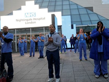 "Medical staff and workers take part in a national ""clap for carers"" to show thanks for the work of Britain's NHS (National Health Service) workers and other frontline medical staff around the country as they battle with the novel coronavirus pandemic, outside of the ExCeL London exhibition centre, which has …"
