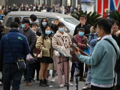 People wearing face masks listen to a performer at a shopping centre in Chengdu, the capital of southwest Sichuan province, on November 28, 2020. (Photo by Noel Celis / AFP) (Photo by NOEL CELIS/AFP via Getty Images)