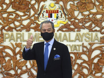 In this photo released by Malaysia's Information Ministry, Prime Minister Muhyiddin Yassin poses for a picture at the parliament, in Kuala Lumpurf, Malaysia Thursday, Nov. 26, 2020. Malaysia's Parliament Thursday approved the government's proposed 2021 budget, throwing a political lifeline to embattled Prime Minister Muhyiddin Yassin amid strong resistance to …