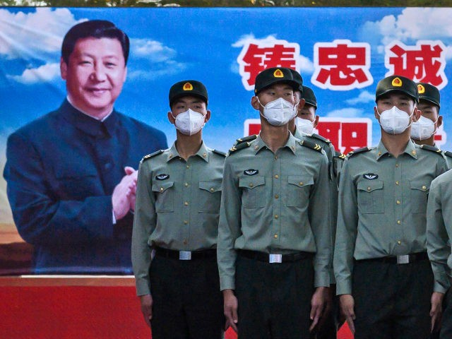 Soldiers of the People's Liberation Army's Honour Guard Battalion wear protective masks as they stand at attention in front of photo of China's president Xi Jinping at their barracks outside the Forbidden City, near Tiananmen Square, on May 20, 2020 in Beijing, China. China's government will open its annual weeklong …